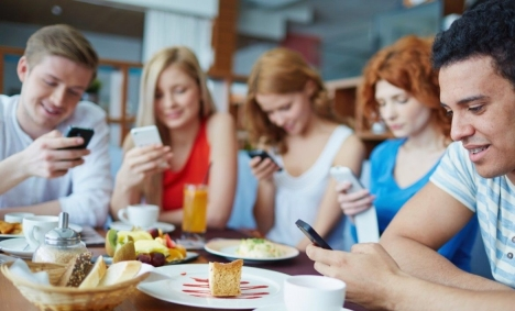 Five people sharing a meal together but interacting with their smartphones rather than each other