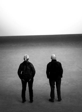 Two men standing on barren ground, looking toward the New Year on the horizon