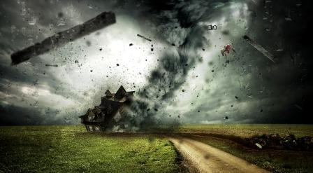 Dark skies with objects hurling in the air and a collapsing house from a cyclone