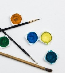 Green, red, blue, yellow paint pots with small, medium and large size artist brushes