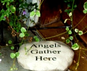 "A stone engraved with the words ""Angels Gather Here"" sits under a pot of vinca vines."
