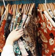 Woman's hand pulling back clothes on rack to see dress