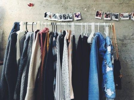 Colored photographs hanging above colored clothes on a rack