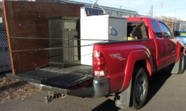 Red pick-up truck loaded with cabinets, chairs, washing machine