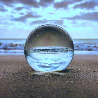Globe sitting on the sand in front of the ocean reflecting the clouds and sand (upside down)