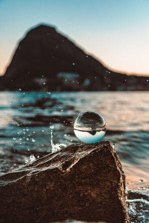 Glass ball sitting on a rock in the ocean being splashed while reflecting sky and sea with mountain in the background