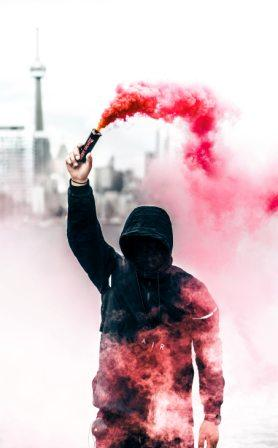 Masked terrorist spreading red smoke into the air