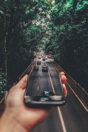 Hand holding a device with cars moving down a main street