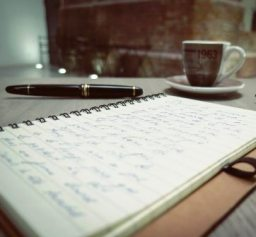 Notebook and pen on table near coffee cup