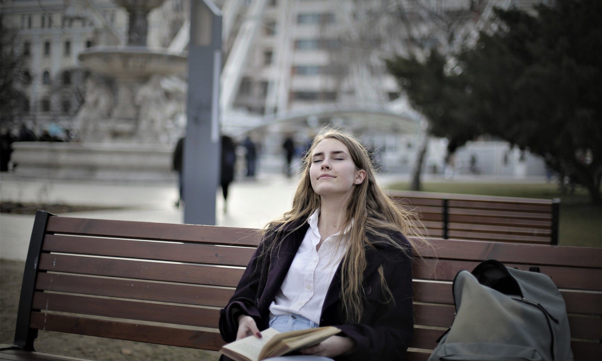 Woman relaxing on a park bench holding a book and breathing in Spring air