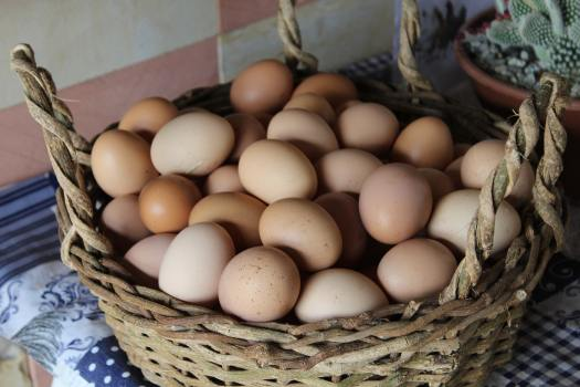 Photo of wooden basket overcrowded with eggs