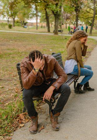 Man and woman turned away from each other on park bench, holding their heads in anger and frustration