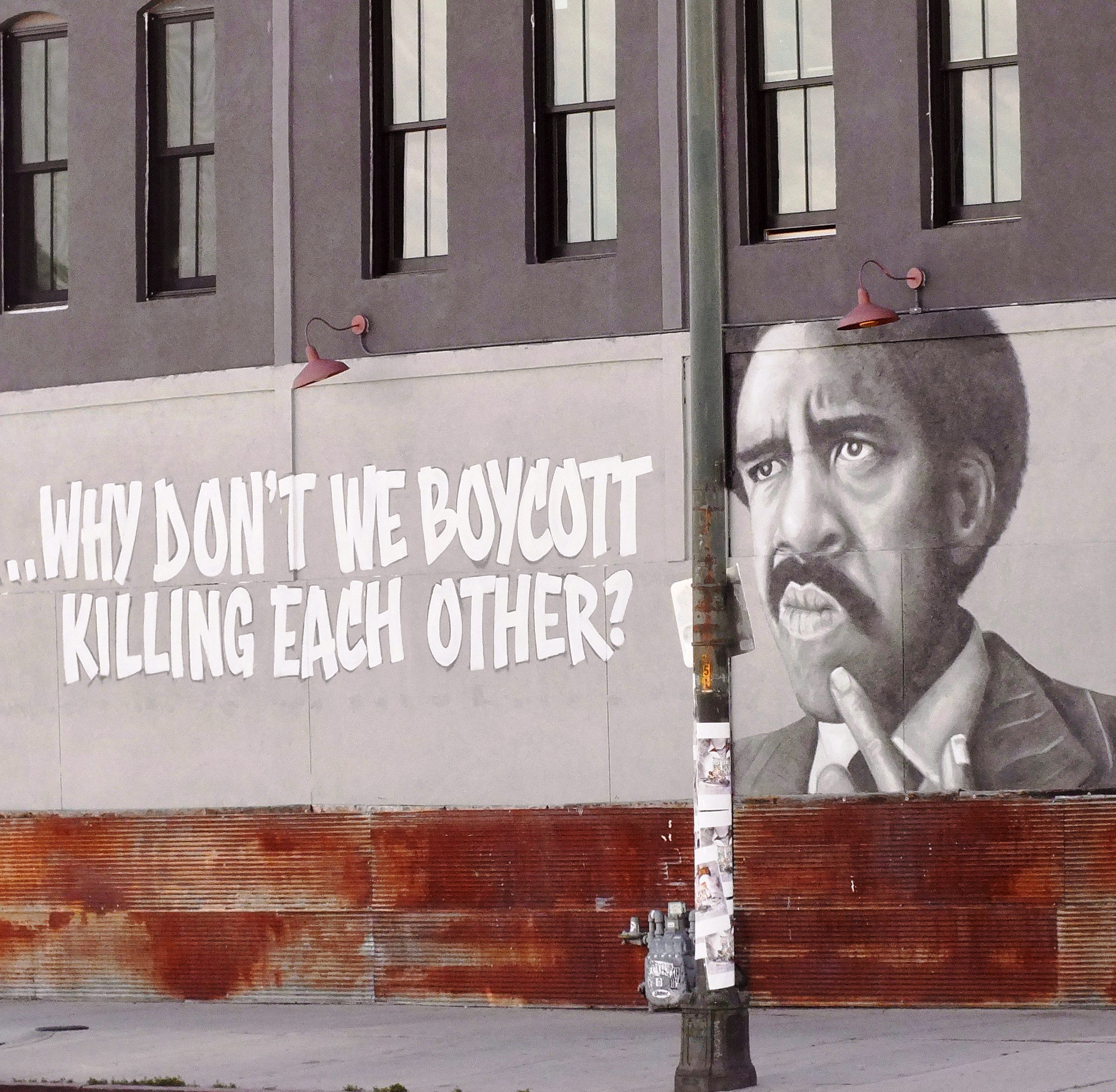 """Street art depicting a black man with the commentary """"...Why don't we boycott killing each other?"""""""