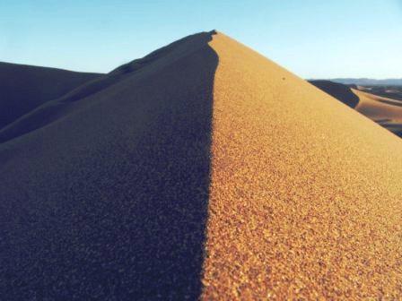 Mountain of sand shadowed over, half dark, half light like a Taijitu