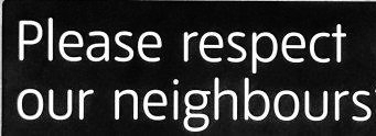 """Black and white sign set on stone indicating """"Please respect our neighbours'"""""""