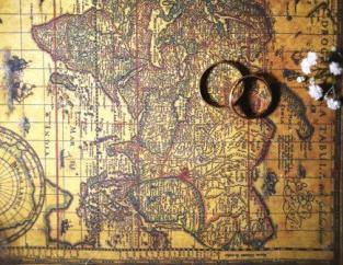 Old world map with wedding rings and flower blossoms