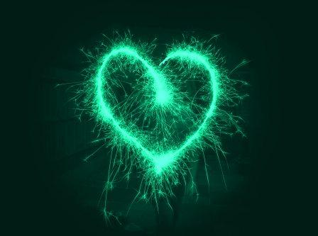 Blue green heart composed of sparks lighting the dark