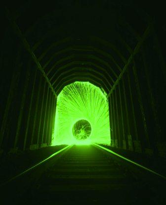 Darkened tunnel with green, healing light at the end
