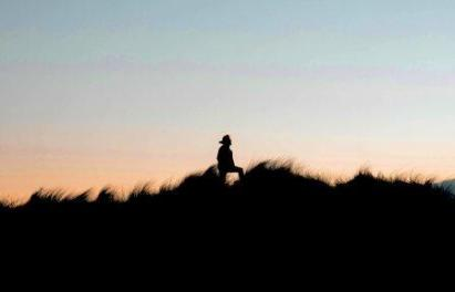 A lone person walking through brush with backdrop of sunrise