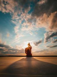 Person meditating on earth's end facing open sky