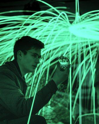 Young male holding a globe reflecting sparks of light, with huge sparks of light in the background