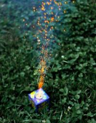 Photo of colorful candle in the green grass emitting uplifting sparks