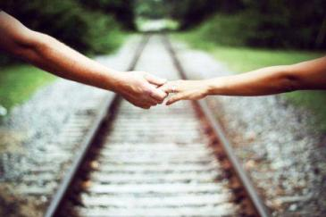 Two hands joined (one with a diamond ring) while facing the path ahead
