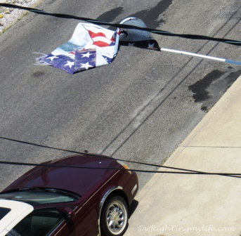 Photo of a car headed toward running over an American Flag on a dirty street