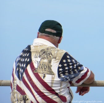 "Photo of man wearing shirt depicting American Flag and inscription ""We the People"""
