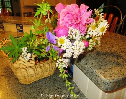 Basket bouquet of peony, daisies, white yarrow, geraniums, purple baptisia