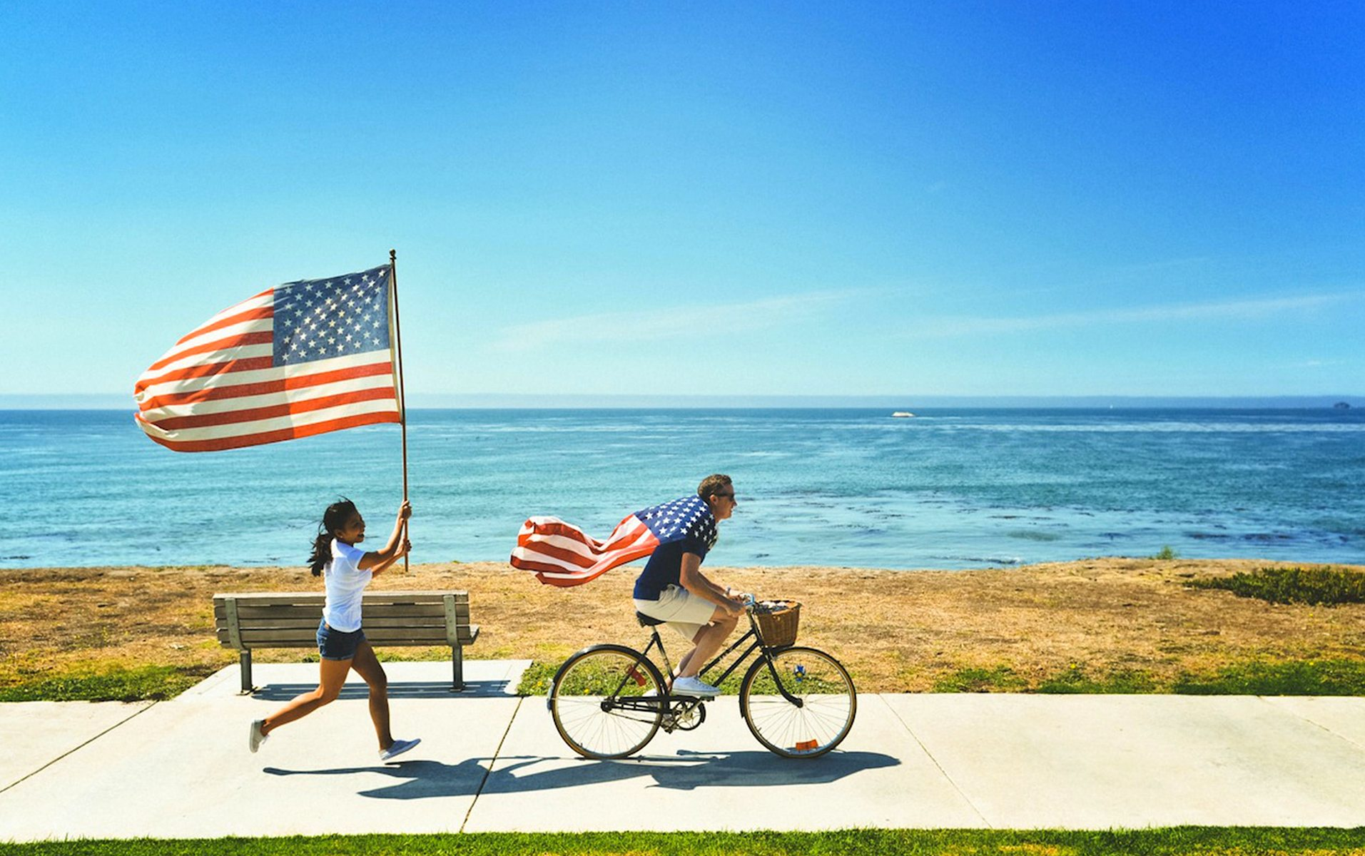 Young girl running with American flag behind man on bicycle wearing an American flag - on a boardwalk near the ocean