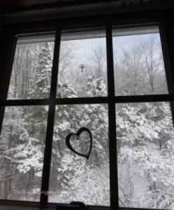 Heart on window looking into winter