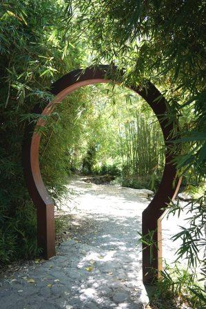 Wooden keyhole arch framing a sunlit path into a garden