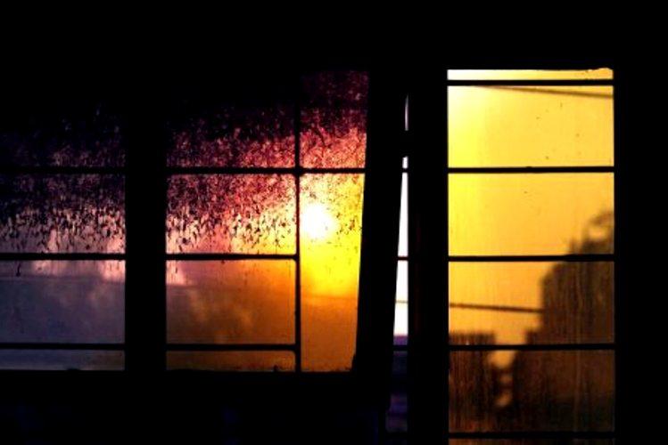 Broken door in darkened room ajar to sunlight