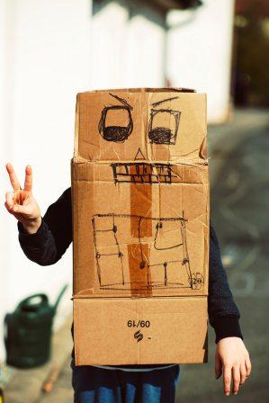 Person making the peace sign while wearing a carboard box with a crayon drawing of a face