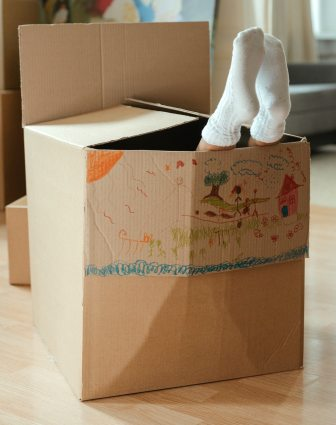 Two feet wearing white socks sticking out of a box decorated with color crayon