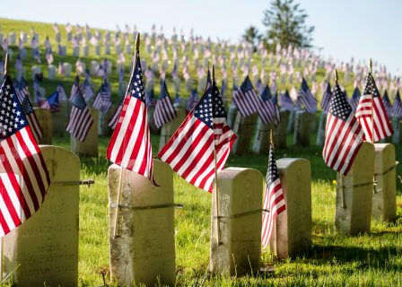 Endless field of tombstones marked by American flags