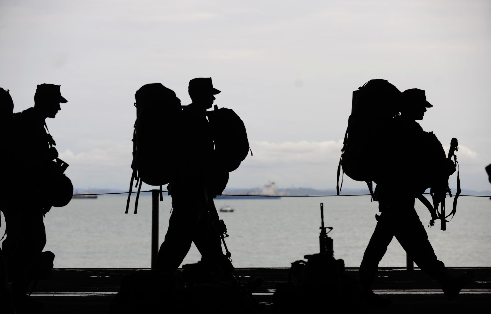 Silhouette of soldiers marching with gear with open water and land in background