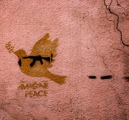 "Textured wall with photo of a gun inside of a dove with the words ""Imagine Peace"""