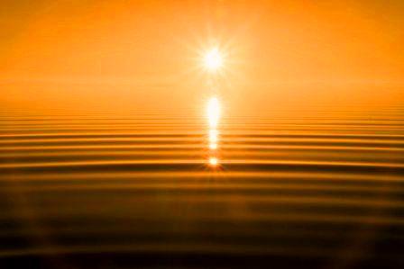 Peaceful ripples on ocean beneath sunset