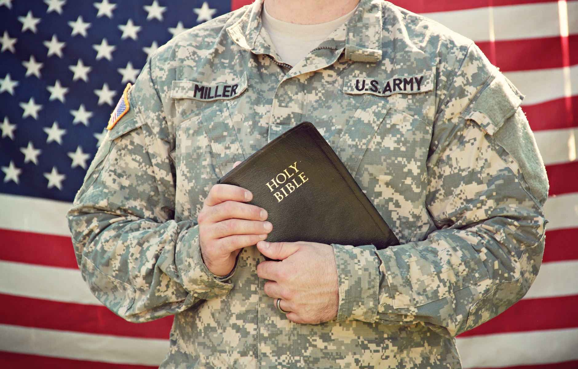 US Soldier holding a Holy Bible with American Flag in the background