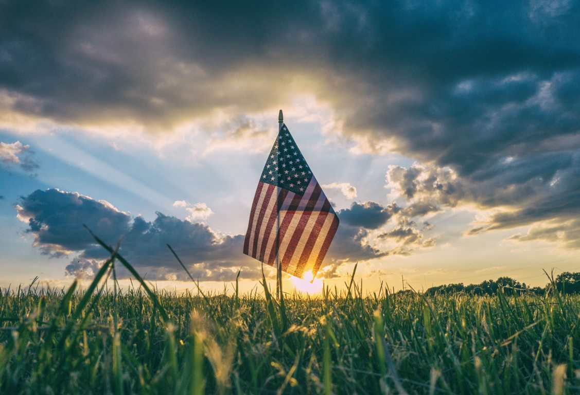 American Flag standing tall in a green field with rising or setting sun in the background and storm clouds overhead