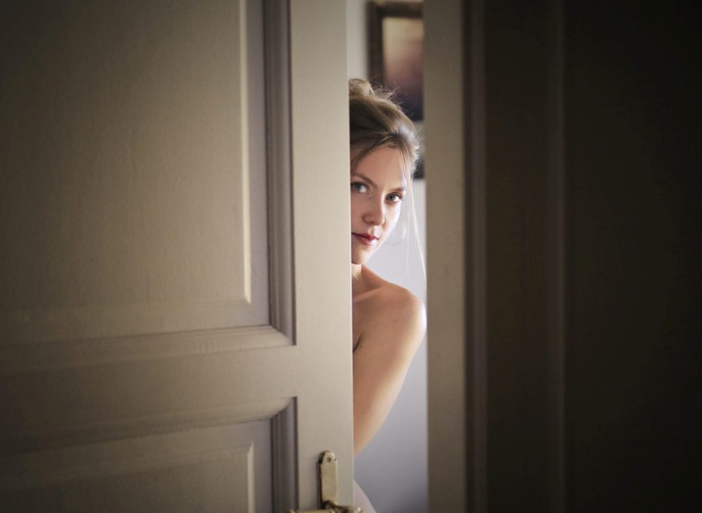 photo of possibly nude woman behind partially closed door