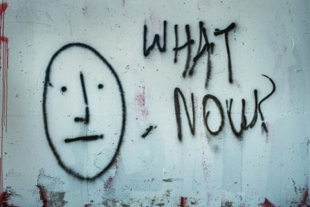 "Drawing on wall of a face and the words ""What now?"""