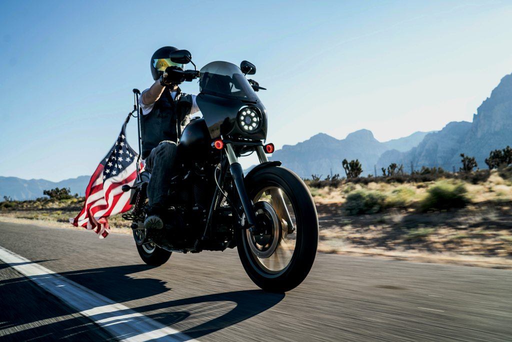 Man on motorcycle riding freely with American Flag behind him in wide open country