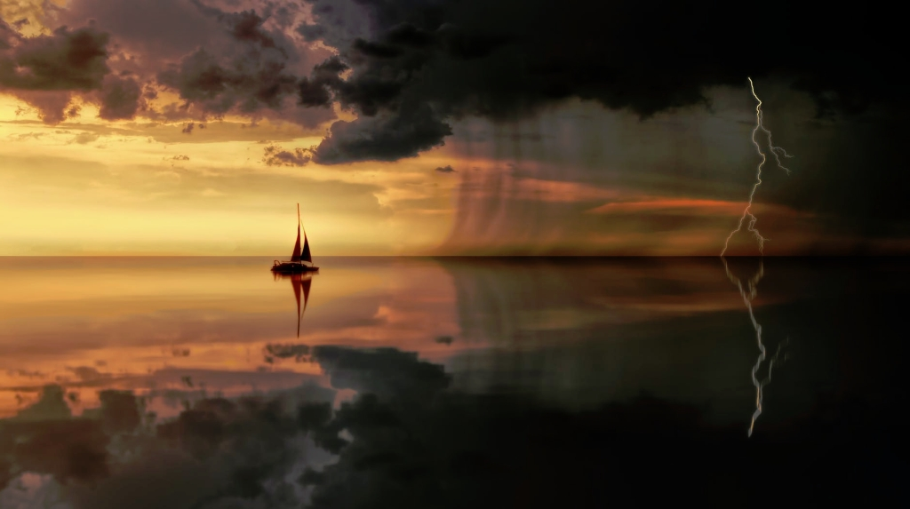 Sailboat in calm waters headed to a darkened storm