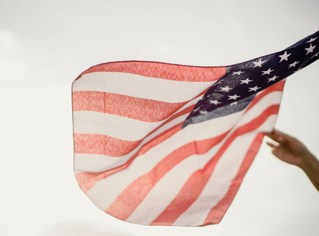 hand trying to straighten contorted American flag