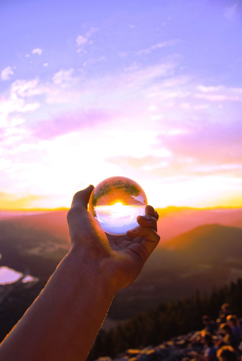 Hand holding globe reflecting a colorful sunrise above a city and country setting