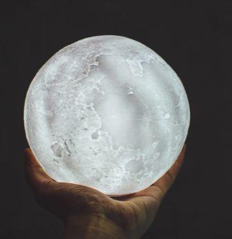 Hand holding an illuminated world globe