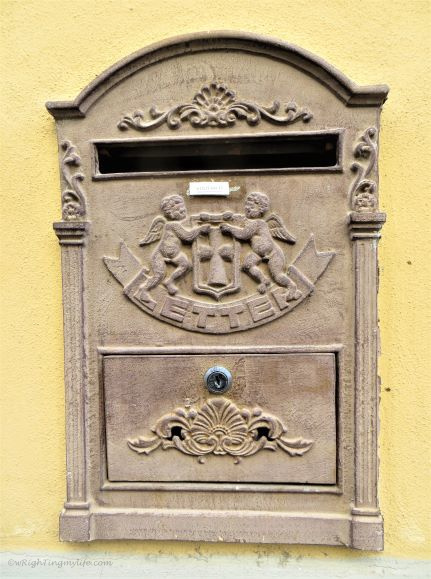 stone relief of cherubs on mailbox in Italy